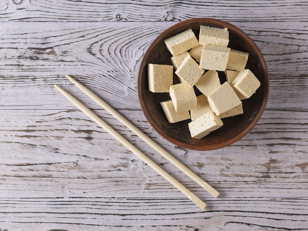 Палочки для еды и кусочки сыра тофу в глиняной миске на деревянном столе. соевый сыр. вегетарианский продукт. плоская планировка.