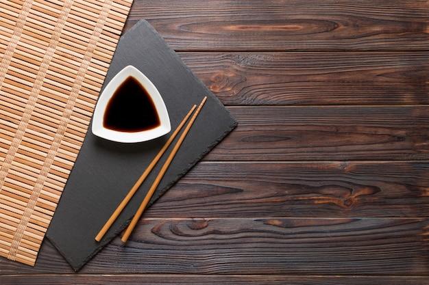 Палочки для еды и соевый соус на черной каменной тарелке, деревянном фоне с копией пространства.