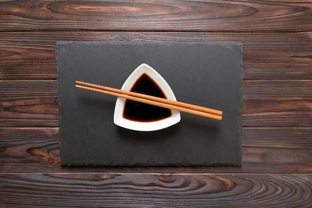 Палочки для еды и соевый соус на черной каменной тарелке, деревянном фоне.