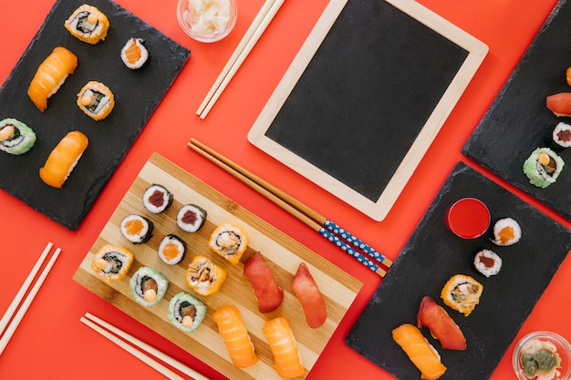 Палочки для еды и суши рядом с доской на красном