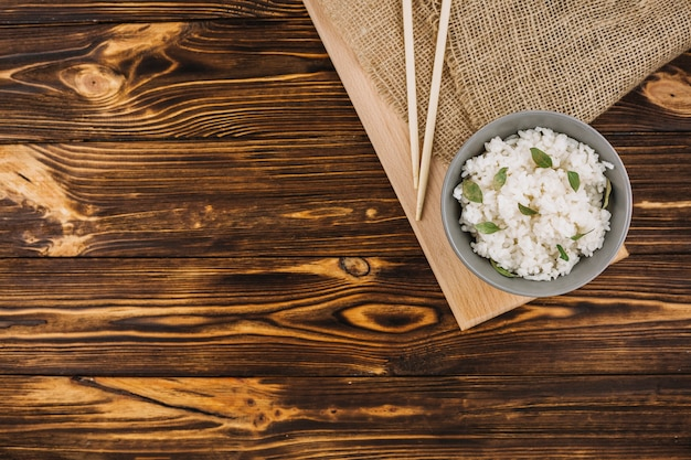 Chopsticks and bowl on board and linen cloth