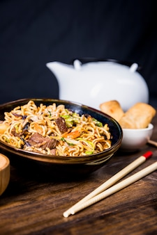 Chopsticks and bowl of delicious noodles with beef on wooden desk