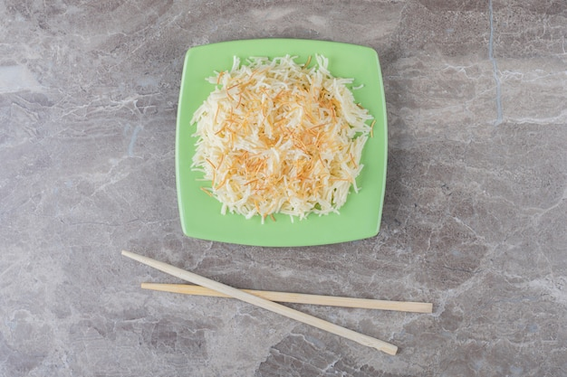 Chopsticks and a bowl of grated pasta and carrot , on the marble.