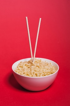 Chopsticks in bowl with noodles