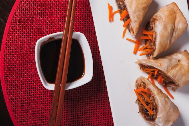 Chopsticks on bowl with sauce near rolls