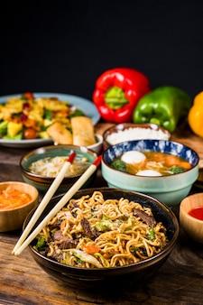 Chopsticks over the bowls of thai cuisine
