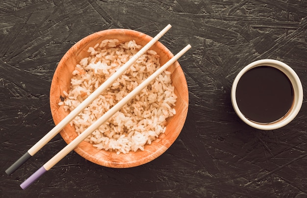 Chopsticks over the cooked rice bowl and soya sauce on background