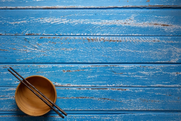 Chopsticks and empty wooden bowls on blue table background, top view with copy space