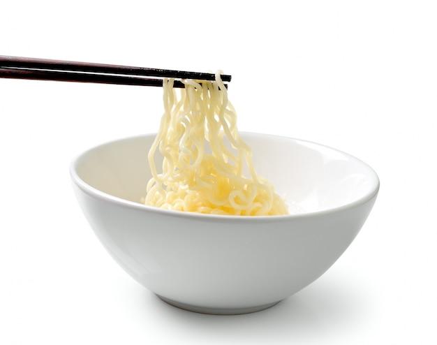 白い背景で隔離の麺を保持している箸