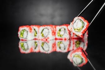 Chopsticks holding roll made of Nori, Pickled rice, Philadelphia Cheese, Cucumber