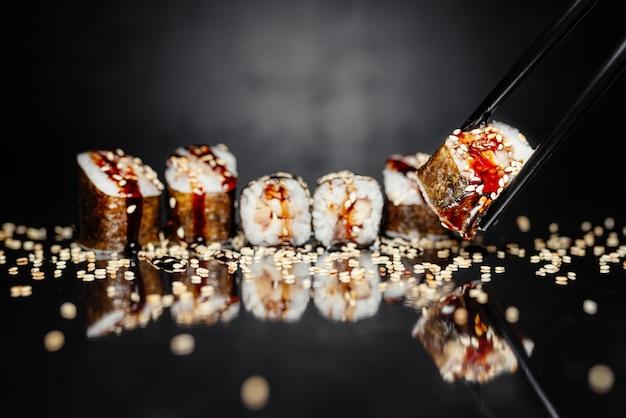 Bacchette che tengono rotolo uguri fatto di nori, riso in salamoia, anguilla / pesce persico unagi
