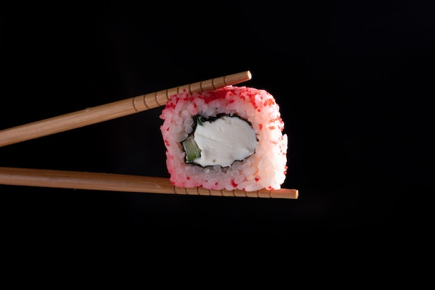 Chopsticks holding seaweed pink roll filled with avocado and fish