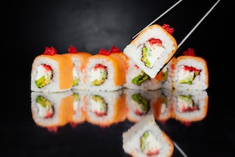 Chopsticks holding sushi roll Philadelphia on black background made of salmon