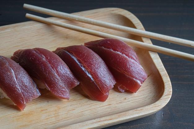 Chopsticks holding tuna nigiri suhi