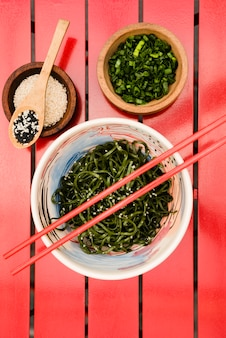 Chopsticks over the japanese chuka seaweed salad served with sesame seeds and chopped spring onions on red table