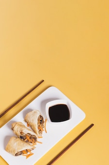Chopsticks near plate with cut rolls