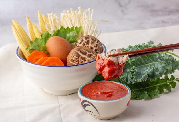 Собранную палочками свинину обмакивают в миску с соусом сукияки. многие овощи в белой миске включают морковь, кукурузу, грибы шиитаке, золотые иглы, сельдерей и куриные яйца.