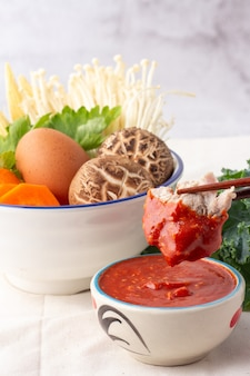 Chopsticks picked pork dipped into a bowl of sukiyaki sauce, many vegetables in white bowl include carrots, baby corn, shiitake mushrooms, golden needles, celery and chicken eggs.