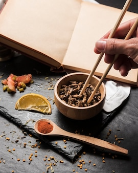 Chopsticks picking larvae from bowl