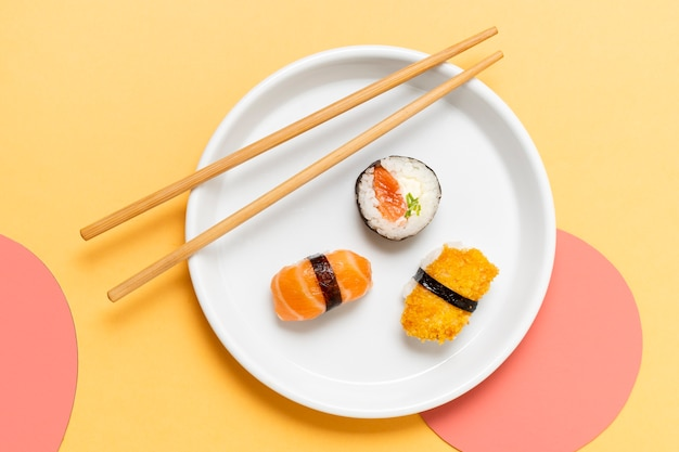 Chopsticks on plate with sushi