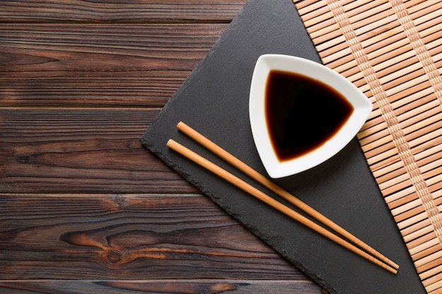Chopsticks and soy sauce on black stone plate, wooden with copy space