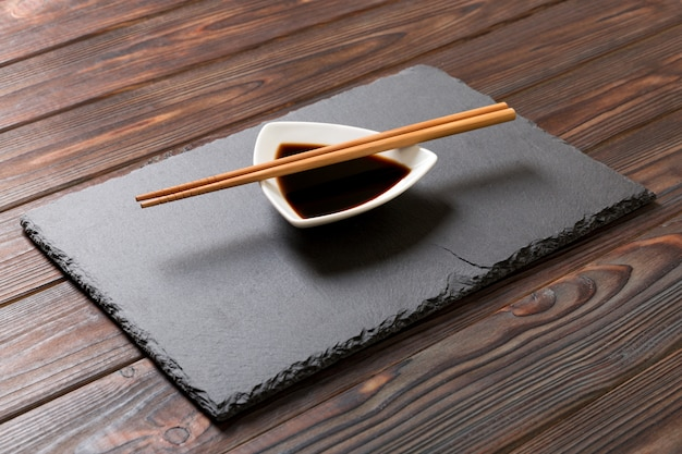 Chopsticks and soy sauce on black stone plate