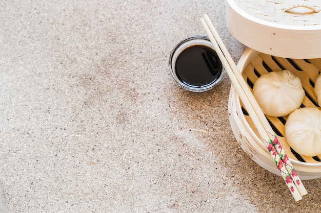 Chopsticks and soy sauce near baozi