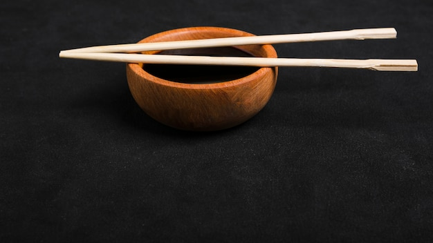 Chopsticks over the soya sauce wooden bowl on black backdrop