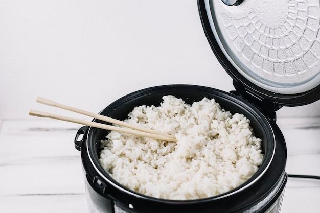 Chopsticks in steamer with rice