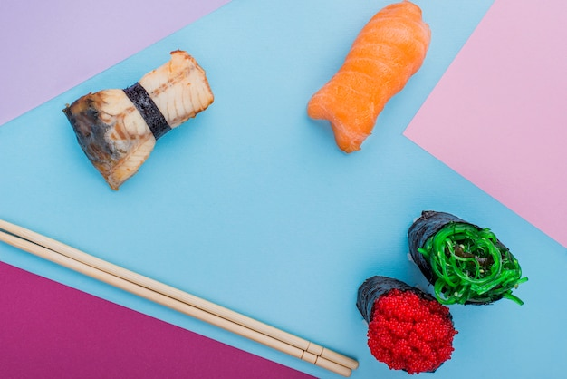 Chopsticks and sushi rolls on table