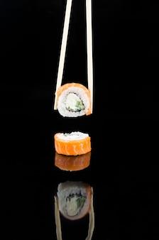 Палочки для еды, принимая суши филадельфия с лососем на черном фоне