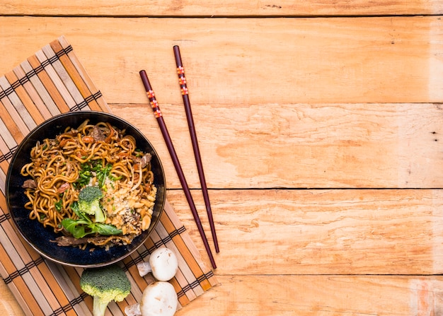 Chopsticks and thai udon noodles with beef and broccoli on wooden table
