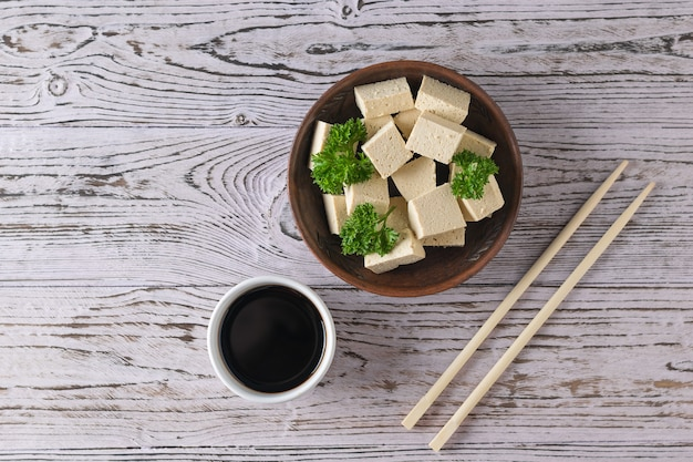 Chopsticks and tofu cheese in a clay bowl on a wooden table. soy cheese. vegetarian product. flat lay.