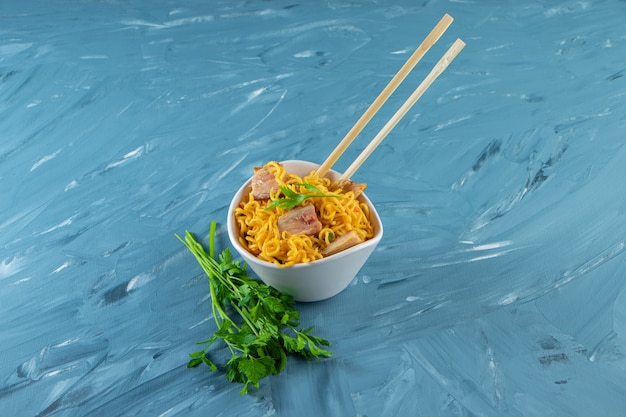 Chopsticks with meat noodles in a bowl next to parsley, on the marble background.