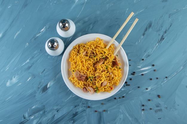 Палочки для еды с мясной лапшой на тарелке, на мраморной поверхности.