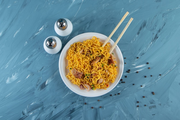 Chopsticks with meat noodles on a plate, on the marble surface.