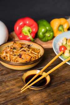 Chopsticks with soya sauce bowl and udon noodles bowl on wooden table
