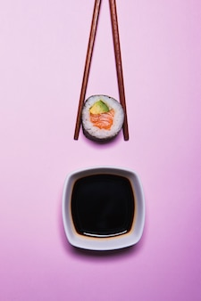 Палочки для еды с суши около соевого соуса