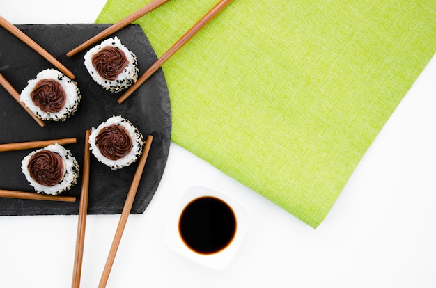 Chopsticks with sushi rolls on a black plate on a white and green background
