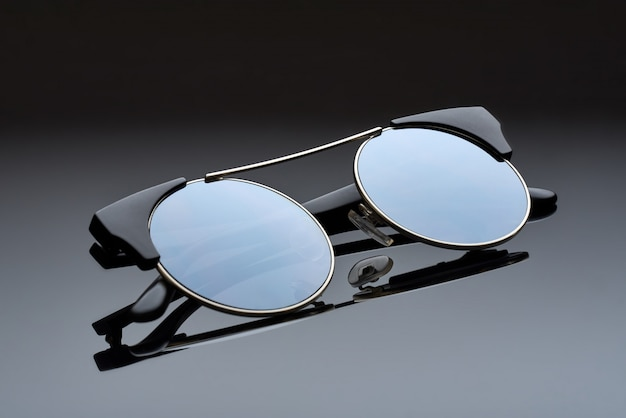 Chor metal glasses with round mirror glasses lie on the reflecting surface.