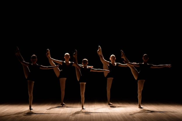 A choreographed dance of a group of graceful pretty young ballerinas practicing on stage in a classical ballet school.