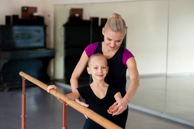 The choreographer teaches the child the ballet positions