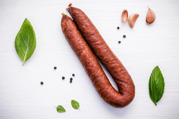Chorizo sartaは木製の背景にバジルの葉でソーセージを薫製した。