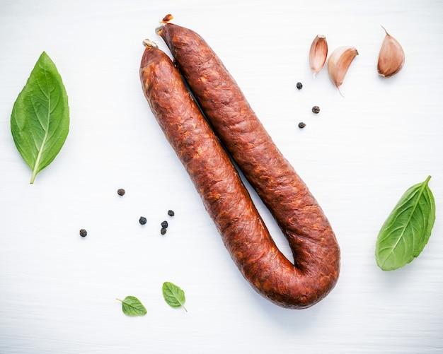 Копченая колбаса chorizo sarta с листьями базилика на деревянном фоне.