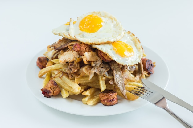 Chorrillana, french fries, fried onion, sausages and fried eggs with white background