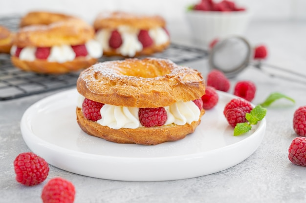 Choux pastries choux rings with cream of cream cheese or cottage cheese and fresh raspberries