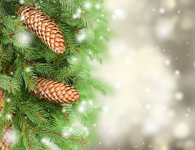 きらめく灰色のお祭りの背景にクリスマスツリーと松ぼっくり