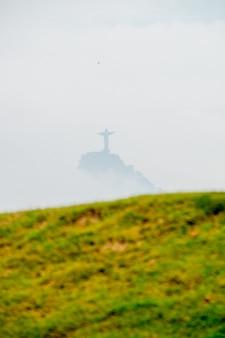 Christ the redeemer among clouds in rio de janeiro, brazil - february 27, 2021: statue of christ the redeemer among clouds seen from flamengo beach in rio de janeiro.