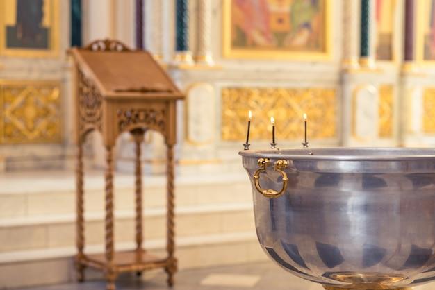 正教会での洗礼式、子供たちの洗礼盤でろうそくを灯す司祭がクローズアップ。