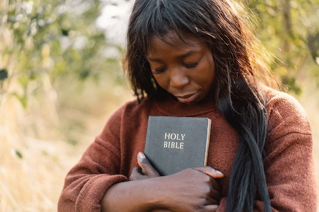 Christian afro girl holds bible in her hands